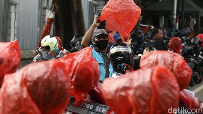 Berbagai cara dilakukan guna mencegah tertular virus Corona. Di Blok M, seorang tukang parkir membungkus ratusan helm konsumennya dengan kantong plastik.