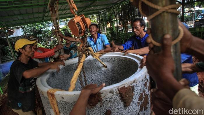 Para pekerja menurunkan gorong-gorong sumur resapan di halaman SMPN 43 Mampang Prapatan, Jakarta, Kamis (10/6/2021).