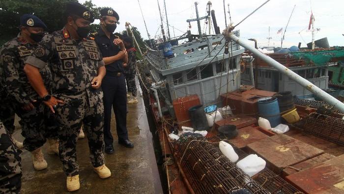Dua petugas Kapal Pengawas Kementerian Kelautan dan Perikanan (KKP) bersiaga di kapal ikan ilegal hasil tangkapan di Stasiun Pengawasan Sumber Daya Kelautan dan Perikanan (PSDKP) Pontianak di Sungai Rengas, Kabupaten Kubu Raya, Kalimantan Barat, Kamis (10/6/2021). Sebanyak 19 kapal ikan ilegal berbendera Malaysia, Vietnam, Filipina dan Indonesia berhasil ditangkap lima kapal pengawas perikanan KKP saat melaksanakan operasi pengawasan di Laut Natuna Utara dan Laut Sulawesi pada 3-8 Juni 2021. ANTARA FOTO/Jessica Helena Wuysang/foc.