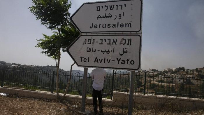 An Israeli man watches efforts to control a wildfire behind the village of Abu Gosh near Jerusalem, Wednesday, June 9, 2021. (AP Photo/Maya Alleruzzo)