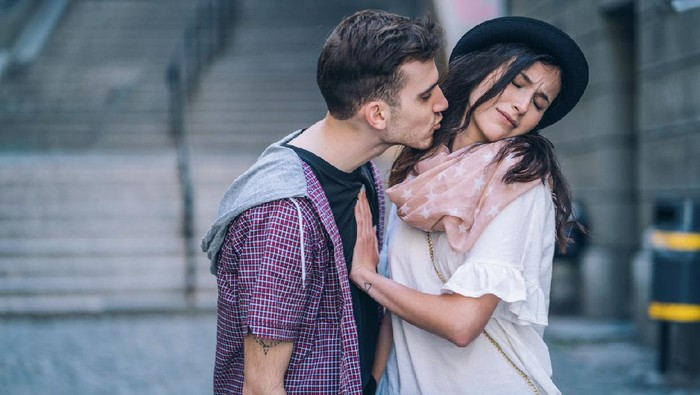 Attractive woman ignoring and pushing away young male that is trying to kiss her