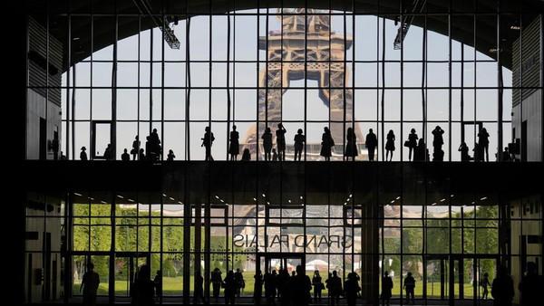 Pada hari pertama Prancis membuka pintunya untuk turis asing, wisatawan berkumpul di Grand Palais dengan latar Menara Eiffel. (AP)
