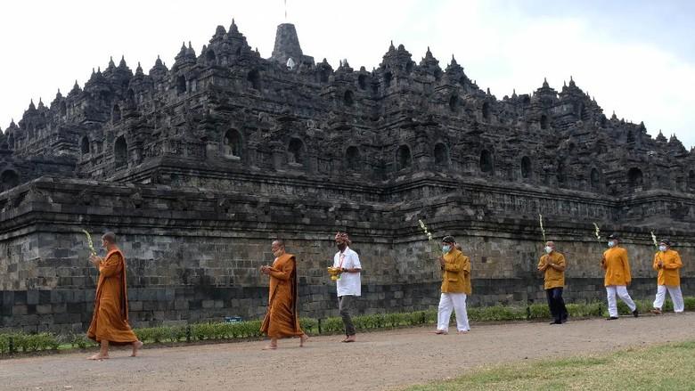 Sejumlah umat Budha melaksanakan Pradaksina (berjalan mengelilingi) candi Borobudur saat upacara Upostha Mandala Puja di kawasan Taman Wisata Candi (TWC) Borobudur, Magelang, Jawa Tengah, Kamis (10/6/2021). Ritual Uphosata Mandala Puja rutin dilaksanakan dua kali dalam sebulan yaitu pada tanggal satu dan tanggal lima belas penanggalan Jawa untuk membersihkan pikiran dari hal-hal kotor. ANTARA FOTO/Anis Efizudin/hp.