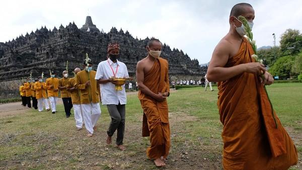 Sejumlah umat Buddha melaksanakan Pradaksina (berjalan mengelilingi) candi Borobudur saat upacara Upostha Mandala Puja di kawasan Taman Wisata Candi (TWC) Borobudur, Magelang, Jawa Tengah, Kamis (10/6/2021).