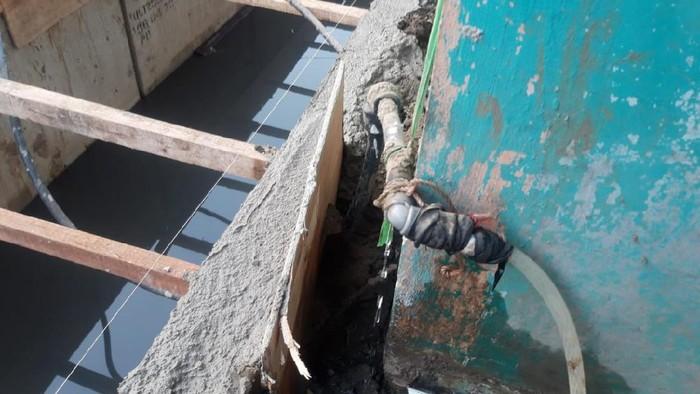 Warga Cakung Barat yang terdampak gangguan air PAM menyambung selang ke pipa yang tidak bermasalah.