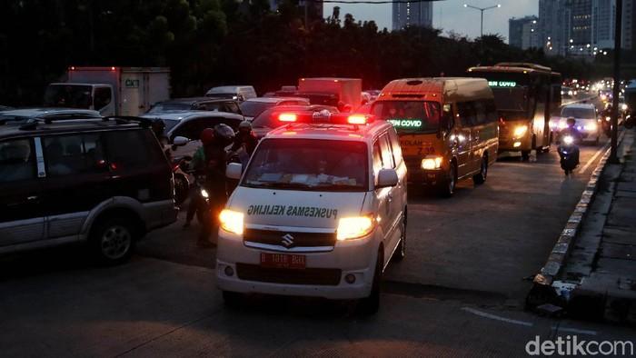 Sejumlah kendaraan ambulans dan bus sekolah yang membawa pasien COVID-19 antre untuk masuk kawasan Rumah Sakit Darurat  COVID-19 (RSDC) Wisma Atlet, Jakarta, Kamis (10/6).