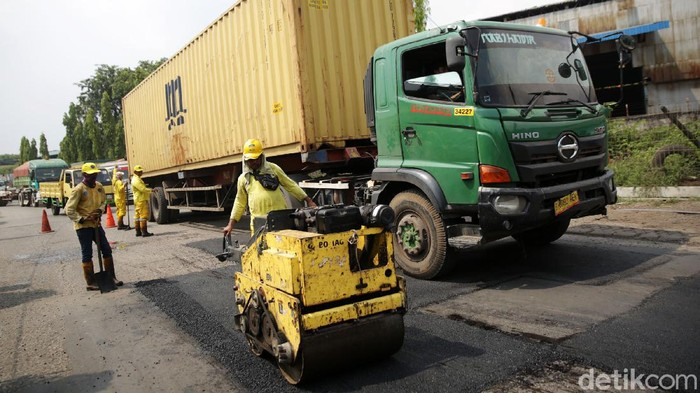 Petugas Bina Marga melakukan pengaspalan jalan yang berlubang di Jalan Akses Marunda, Jakarta Utara, Jumat (11/6/2021). Pengaspalan jalan yang sering rusak karena dilalui kendaraan berat ini dilakukan guna memberikan kenyamanan para pengguna jalan.