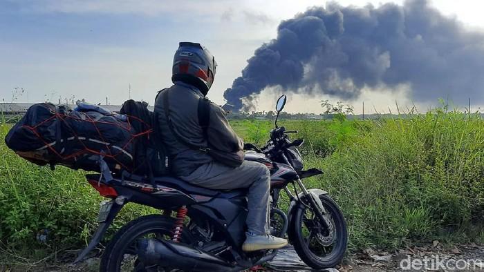 Kepulan asap yang membumbung ke arah barat dari tangki Kilang Pertamina RU IV Cilacap yang terbakar sejak Jumat (11/6) malam menjadi tontonan warga sekitar. Warga yang penasaran semakin sore semakin banyak.