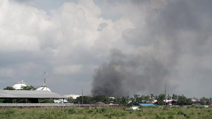 Asap hitam terlihat terlihat mulai menghilang sesaat sebelum api berhasil dipadamkan, di Kilang Pertamina RU IV Cilacap, Jawa Tengah, Minggu (13/6/2021). Tim pemadam berhasil memadamkan seluruh api pada pukul 10.50 WIB di sekitar tangki area 39 Kilang RU IV Cilacap, dan masih terus dilakukan pemantauan serta pendinginan guna memastikan tidak ada lagi titik api baru. ANTARA FOTO/Idhad Zakaria/foc.