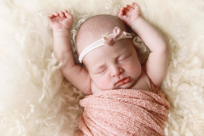 The newborn was wrapped in a green cloth and was placed on a soft rubber mat with a blurred background.