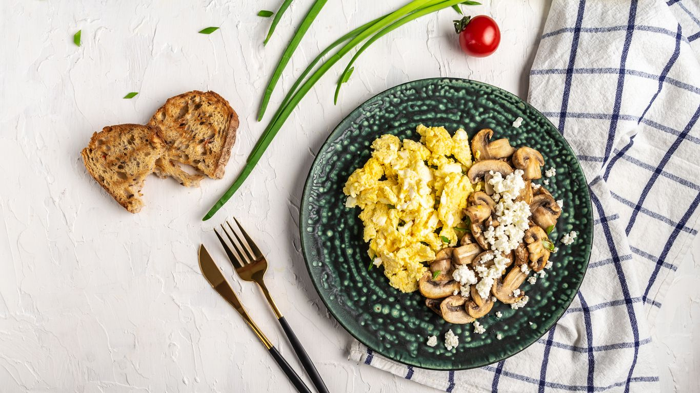 Scrambled Eggs with Mushrooms and Cottage Cheese. Delicious breakfast or snack on a light background, top view.