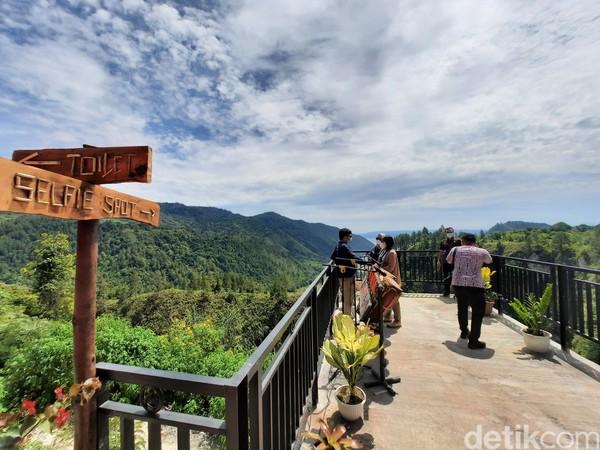Rest Area Adian Nalambok menyediakan spot foto yang memungkinkan wisatawan untuk mengabadikan hijaunya hutan dan birunya Danau Toba tersebut.