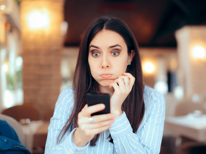 Stressed young woman checking her phone in a restaurant