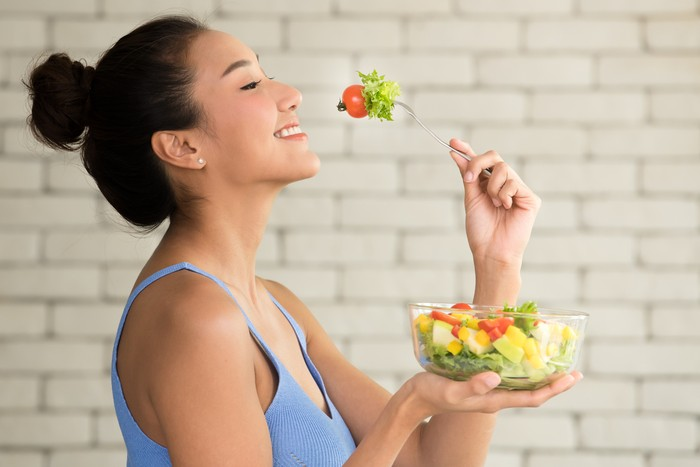 Asian woman in joyful postures with hand holding salad bowl