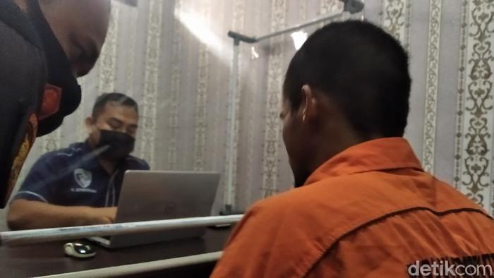 Pria inisial AK (berbaju orange) yang tega menghabisi nyawa istri dan anaknya (Suriyatman/deticom).