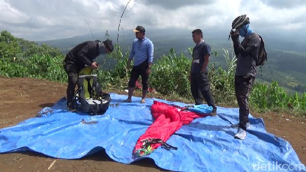Setelah jalan kaki 15 menit, traveler akan tiba di puncak gunung Wayang. Dari puncak inilah, traveler bisa menjajal olahraga paralayang. Sebelum terbang, semua peralatan dicek dulu ya!