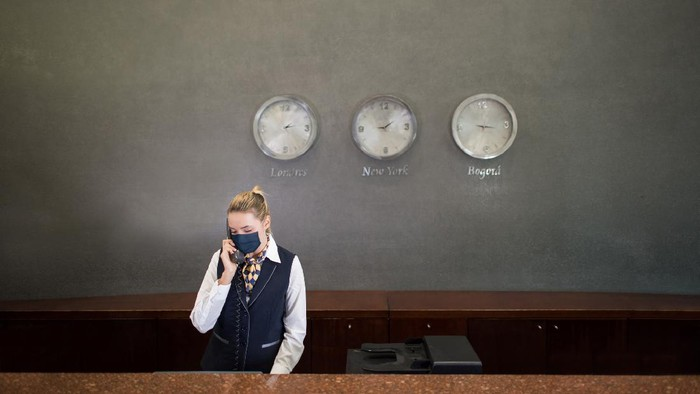 Resepsionis hotel memakai masker saat pandemi virus Corona.
