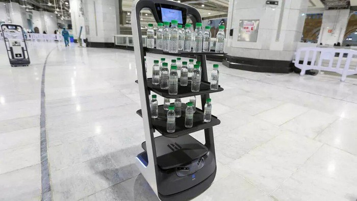 Rolling robots have been deployed to ensure pilgrims have access to holy water without human contact - AFP