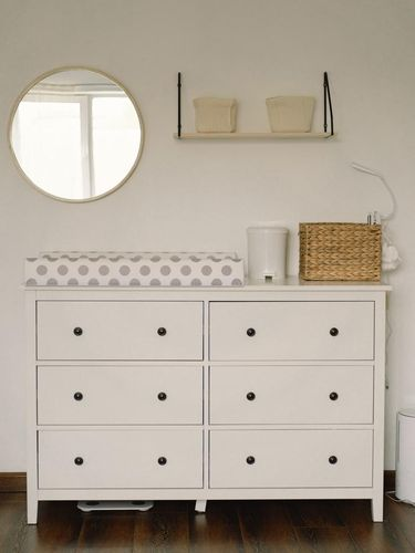 Baby room interior design. Chest of drawers with changing pad and tray in nursery. Infant baby room.