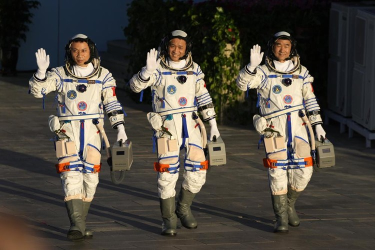 Chinese astronauts, from left, Tang Hongbo, Nie Haisheng, and Liu Boming wave as they prepare to board for liftoff at the Jiuquan Satellite Launch Center in Jiuquan in northwestern China, Thursday, June 17, 2021. China plans on Thursday to launch three astronauts onboard the Shenzhou-12 spaceship who will be the first crew members to live on Chinas new orbiting space station Tianhe, or Heavenly Harmony. (AP Photo/Ng Han Guan)