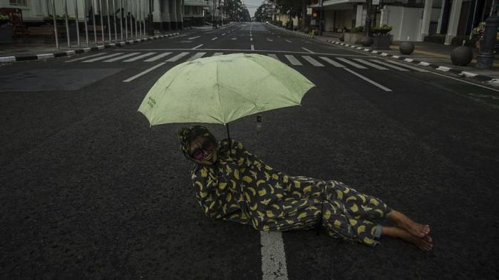 Cosplayer hantu berdiri di tengah ruas jalan protokol kawasan Asia Afrika yang ditutup di Bandung, Jawa Barat, Jumat (18/6/2021). Warga menikmati suasana ruas jalan protokol di Kota Bandung yang lengang setelah ditutup untuk menekan peningkatan kasus aktif COVID-19 dan status siaga satu kawasan Bandung Raya. ANTARA FOTO/Novrian Arbi/rwa.