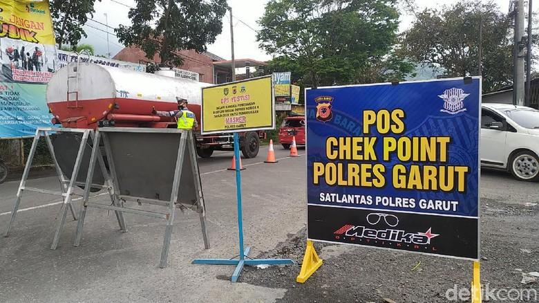 Petugas gabungan melakukan penyekatan kendaraan wisatawan di perbatasan Garut-Bandung. Puluhan kendaraan terpaksa putar balik.
