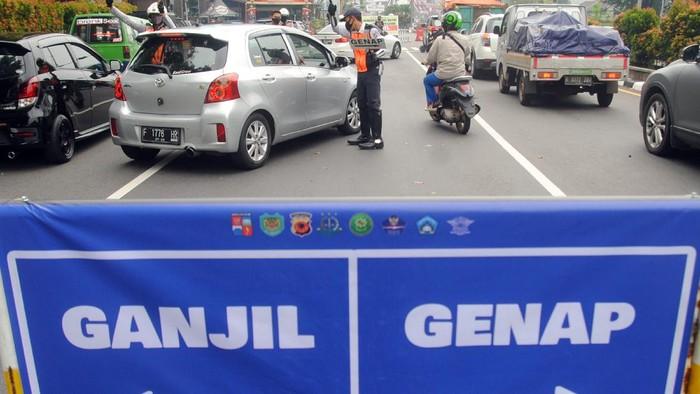 Petugas gabungan mengatur lalu lintas saat pemberlakuan aturan ganjil genap di Jalan Pajajaran, Kota Bogor, Jawa Barat, Sabtu (19/6/2021). Pemkot Bogor kembali memberlakukan aturan ganjil genap untuk kendaraan roda dua dan empat pada setiap akhir pekan untuk mengurangi mobilitas warga sekaligus mengendalikan lonjakan kasus positif COVID-19 di Kota Bogor yang mencapai 204 kasus pada Kamis (17/6/2021). ANTARA FOTO/Arif Firmansyah/rwa.
