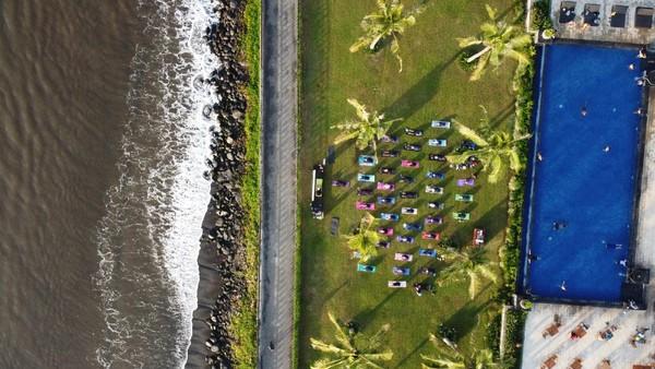 Foto udara warga melakukan yoga di Pantai Ketapang Indah, Banyuwangi, Jawa Timur, Sabtu (19/6/2021).