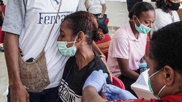 Reaksi seorang atlet Papua saat disuntik vaksin COVID-19 oleh petugas medis di Wisma Atlit Mandala Jayapura, Kota Jayapura, Papua, Sabtu (19/6/2021). Koordinator medis Komite Olahraga Nasional Indonesia (KONI) Papua Billy Haumasse mengatakan tahap pertama vaksinasi kepada atlet Papua, panitia PON XX Papua dan official-official, hari pertama mencapai 300-an orang, sedangkan yang tak memenuhi syarat vaksin berjumlah 10 orang. ANTARA FOTO/Indrayadi TH/rwa.