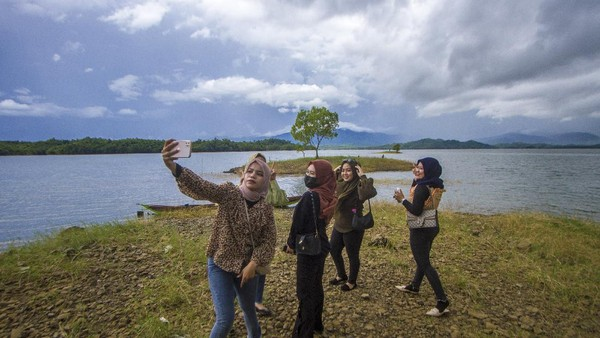 Pengunjung berswafoto dengan latar belakang Waduk Riam Kanan di Kawasan Wisata Bukit Batu, Desa Sungai Luar Tiwingan Baru, Kabupaten Banjar, Kalimantan Selatan, Sabtu (19/6/2021).