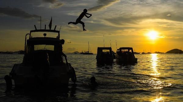 Seorang anak melompat dari atas kapal di Pantai Pede, Labuan Bajo, Manggarai Barat, Nusa Tenggara Timur, Sabtu (19/6/2021).