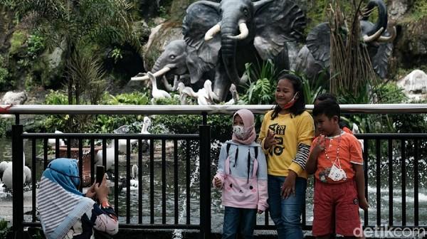 Sejumlah pengunjung berfoto di kawasan Taman Margasatwa Ragunan, Jakarta, Minggu (20/6/2021).
