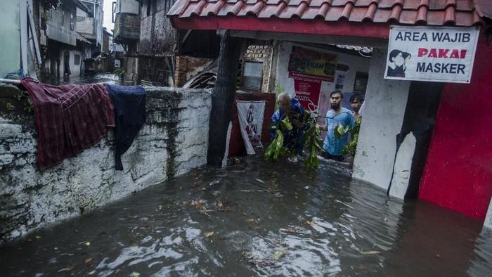 Seorang anak berdiri di atas pagar rumahnya yang terendam banjir di kawasan Kacapiring, Bandung, Jawa Barat, Senin (21/6/2021). Puluhan rumah di kawasan tersebut terendam banjir setinggi 30 cm hingga dua meter akibat intensitas curah hujan yang tinggi dan luapan Sungai Cikudapateuh Dalam. ANTARA FOTO/Novrian Arbi/wsj.