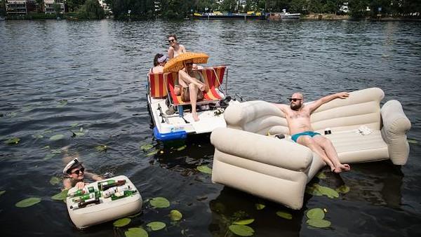 Seorang pria berjemur di perahu karet berbentuk sofa di sungai Spree, Berlin, Jerman. Getty Images/Steffi Loos