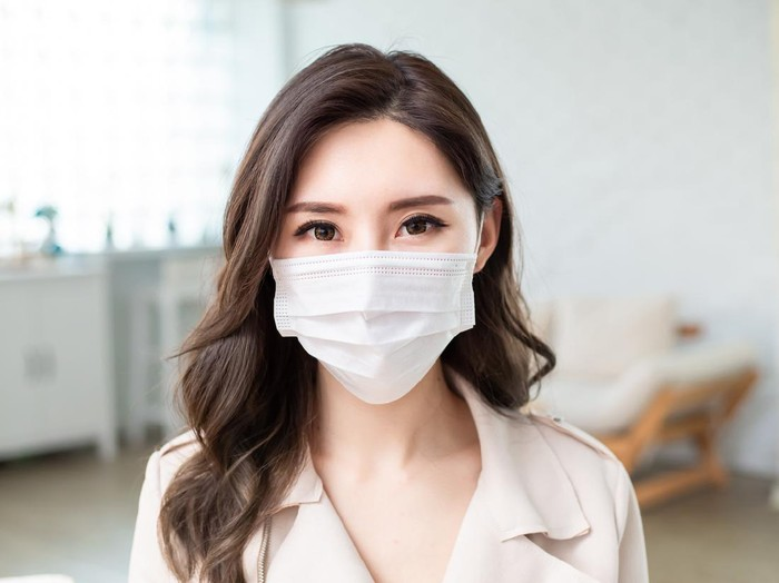 Asian Woman wears a facial mask and she look you