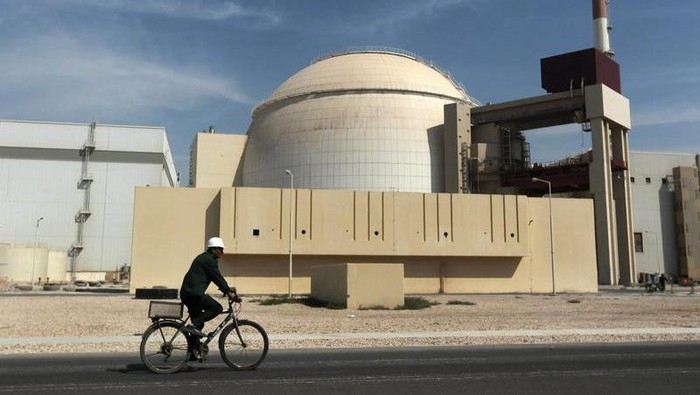 FILE - In this Oct. 26, 2010 file photo, a worker rides a bicycle in front of the reactor building of the Bushehr nuclear power plant, just outside the southern city of Bushehr. Iran's sole nuclear power plant has undergone a temporary emergency shutdown, state TV reported on Sunday, June 20, 2021. An official from the state electric energy company, Gholamali Rakhshanimehr, said on a talk show that the Bushehr plant shutdown began on Saturday and would last