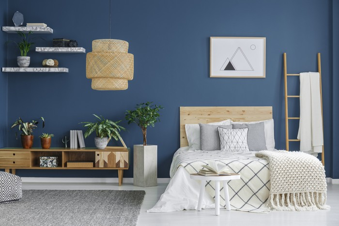 Cozy bedroom interior with a double bed, wooden cabinet, chandelier and blue wall