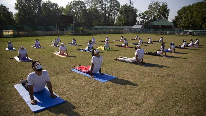 Kashmiri students perform yoga as they mark International Yoga Day in Srinagar, Indian controlled Kashmir, Monday, June 21, 2021. (AP Photo/Mukhtar Khan)