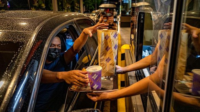 SAN FERNANDO, PHILIPPINES - JUNE 18: A customer poses for a picture wearing a mask with the face of Jungkook of BTS, during the launch of the BTS Meal at a McDonald's restaurant on June 18, 2021 in San Fernando, Pampanga province, Philippines. Long queues formed in several McDonald's restaurants in the Philippines as fans of the K-pop group BTS flocked to order the newly launched and wildly popular BTS themed meals. The limited edition celebrity meal