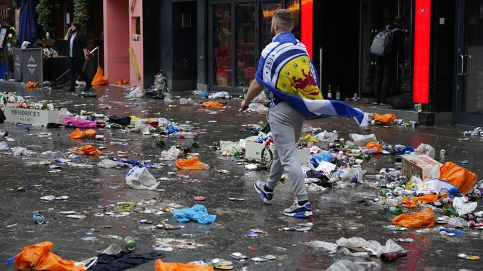 Police officers stand amongst rubbish left behind by partying Scotland fans near the statue to William Shakespeare in Leicester Square in London, Friday, June 18, 2021 prior to the Euro 2020 soccer championship group D match between England and Scotland at Wembley Stadium. (AP Photo/Kirsty Wigglesworth)