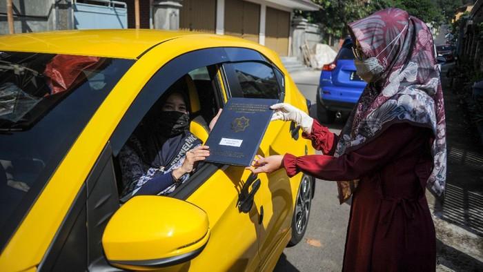 Sebuah sekolah di Sumedang gunakan sistem drive thru saat pembagian rapot para muridnya. Hal itu dilakukan sebagai salah satu upaya mencegah penyebaran Corona.