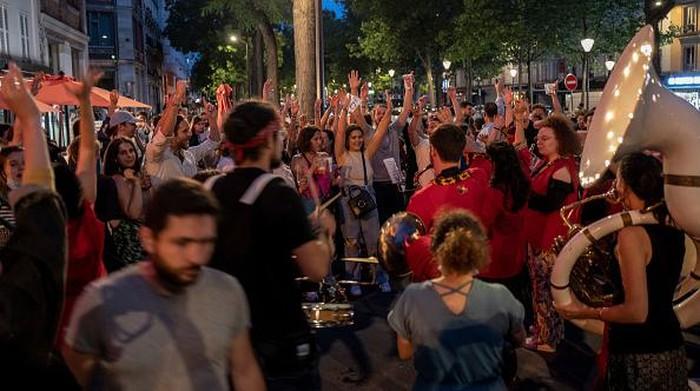 Warga padati jalanan di Paris untuk rayakan festival musik. Prancis telah longgarkan aturan pemakaian masker di ruang terbuka usai kasus COVID-19 dinilai turun.