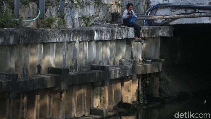 Sejumlah warga tampak memancing di bantaran kali di kawasan Cempaka Putih, Jakarta Timur, Selasa (22/6/2021).