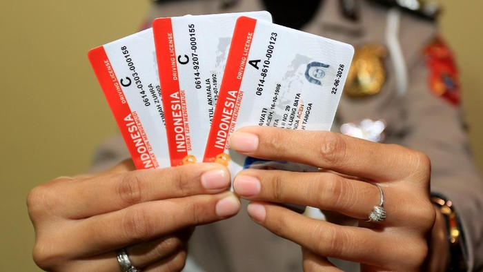 Petugas menunjukkan Surat Izin Mengemudi (SIM) seusai proses pembuatan di Kantor Satuan Penyelenggara Administrasi SIM (Satpas SIM) Polresta Banda Aceh, Aceh, Selasa (22/6/2021). Kepolisian Polda Aceh menyatakan pengurusan Surat Izin Mengemudi (SIM) dan Surat Keterangan Catatan Kepolisian (SKCK) tidak perlu menyertakan surat keterangan dan sertifikat vaksin COVID-19. ANTARA FOTO/Syifa Yulinnas/hp.