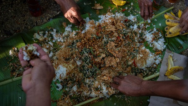 Usai membersihkan mata air, tradisi berlanjut dengan menggelar makan bersama.