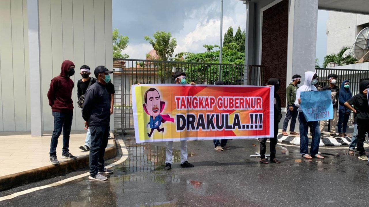 Pedemo bawa spanduk gambar Gubernur Riau, Syamsuar, yang diedit menjadi drakula (Raja Adil-detikcom)