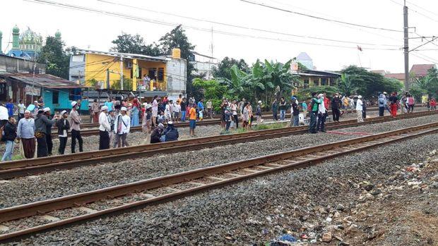 Pendukung HRS berkerumun di rek kereta dekat Stasiun Klender