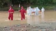 Petugas Pakai APD Panggul Jenazah Lewati Sungai-Persawahan