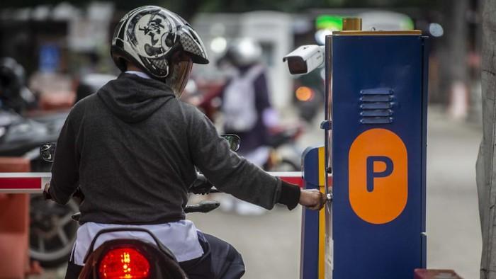 Pengendara sepeda motor mengambil karcis parkir di lapangan IRTI Monas, Jakarta Pusat, Jakarta, Rabu (23/6/2021). Pemerintah Provinsi DKI Jakarta berencana menaikkan tarif layanan parkir dengan tarif tertinggi Rp60 ribu per jam untuk mobil dan Rp18 ribu per jam untuk motor yang bertujuan mendorong warga Jakarta beralih menggunakan transportasi umum. ANTARA FOTO/Aprillio Akbar/hp.