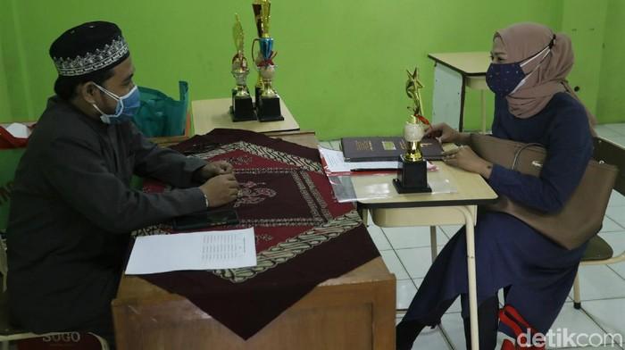 Sebagian sekolah di Kabupaten Bogor bagikan rapor para murid secara tatap muka. Kegiatan itu digelar dengan terapkan protokol kesehatan ketat guna cegah Corona.